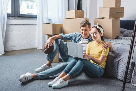 Photo for Happy young couple sitting on floor of bedroom and using laptop while moving into new home - Royalty Free Image