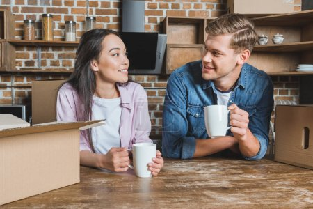 happy young couple drinking coffee at kitchen of new home