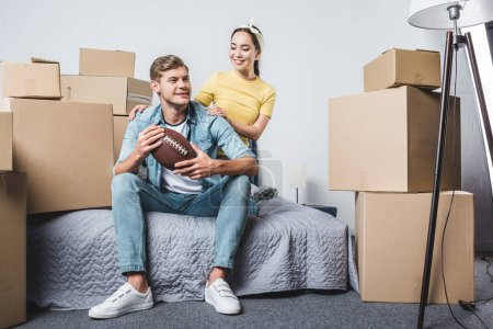 beautiful young couple sitting in bedroom of new home with american football ball