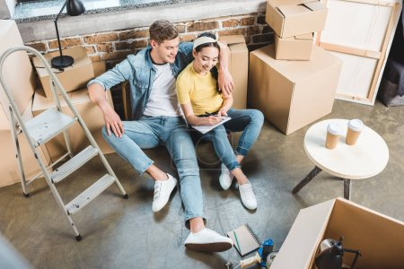 high angle view of young couple sitting on floor while moving into new home