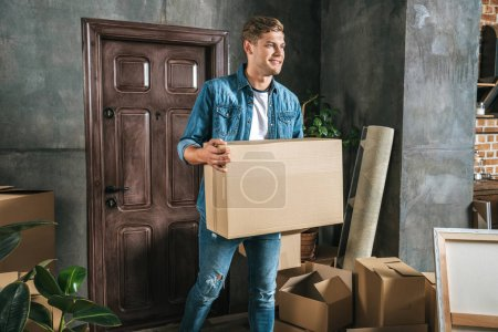 handsome young man carrying box while moving into new house