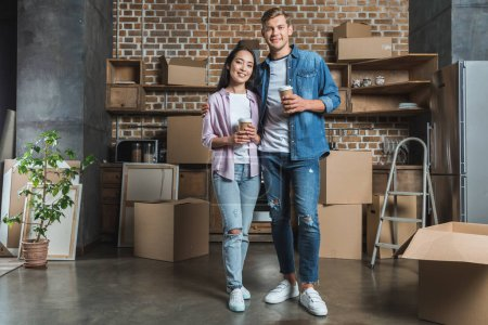 happy young couple with paper cups of coffee standing on kitchen while moving into new home