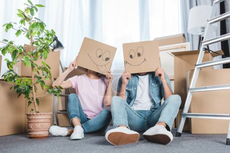 couple sitting on floor after moving into new home with boxes on heads