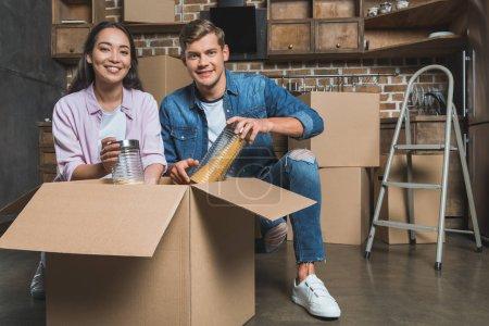 Photo pour Jeune couple déballer des boîtes sur la cuisine tout en déménageant dans une nouvelle maison - image libre de droit