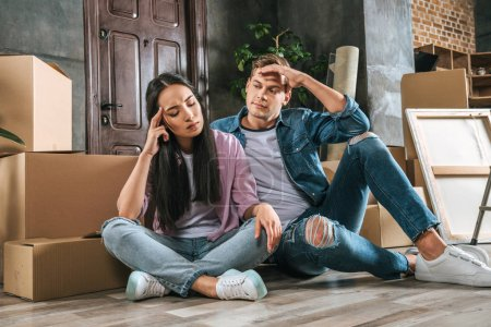 young couple sitting on floor after argument while moving into new home