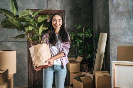Photo pour Heureuse jeune femme avec ficus plante et boîtes déménageant dans une nouvelle maison - image libre de droit