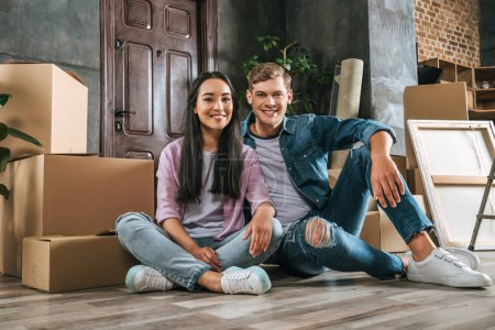 Photo for Attractive young couple sitting on floor together while moving into new home - Royalty Free Image