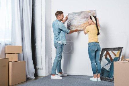 Photo pour Beau jeune couple accrocher photo sur le mur ensemble tout en déménageant dans une nouvelle maison - image libre de droit