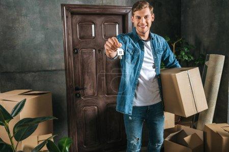 Photo pour Attrayant homme souriant avec boîte et clé déménageant dans une nouvelle maison - image libre de droit