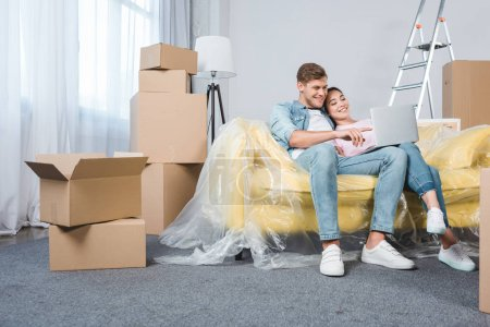 beautiful young couple using laptop together on couch while moving into new home