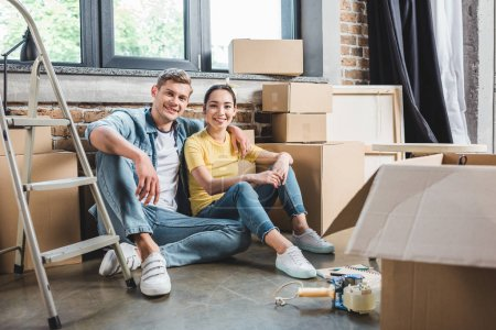 smiling young couple sitting on floor together while moving into new home