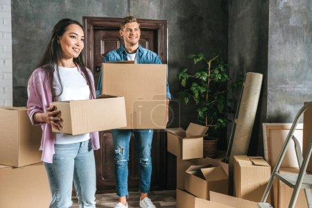beautiful young couple with boxes moving into new home