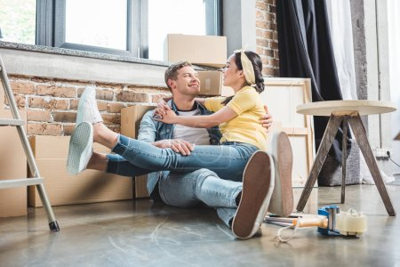 loving young couple sitting on floor together while moving into new home