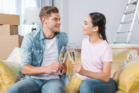 beautiful young couple clinking glasses of champagne while sitting on couch at new home