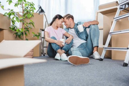 beautiful young couple with mugs sitting on floor at new home