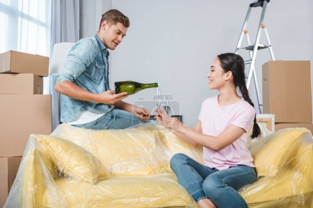 interracial happy couple drinking champagne after moving into new home