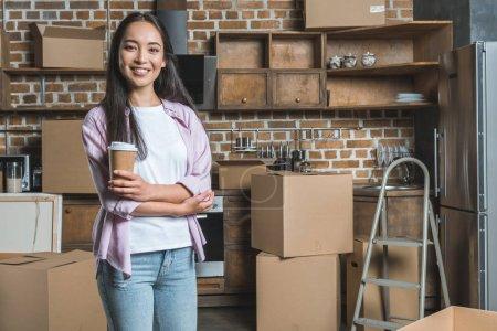 Photo pour Jeune femme souriante avec tasse en papier de café et boîtes debout sur la cuisine de la nouvelle maison - image libre de droit