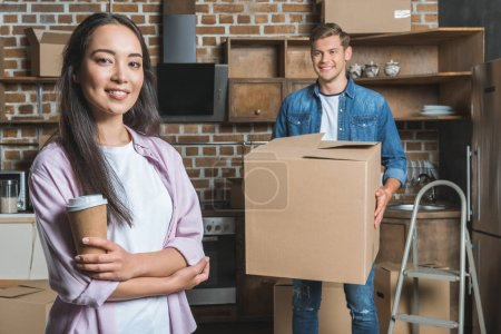 beautiful young couple with boxes and coffee to go moving into new home