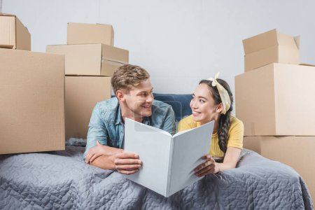 happy young couple with photo album lying on bed while moving into new home