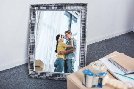 Photo pour Miroir reflet de beau couple embrassant après avoir déménagé dans une nouvelle maison - image libre de droit