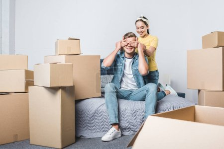 young asian woman making surprise for boyfriend while moving into new home