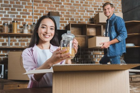 Photo for Beautiful young couple unpacking boxes during moving into new home - Royalty Free Image