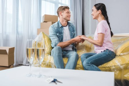 beautiful young couple sitting on couch and holding hands after moving into new home with champagne glasses on foreground