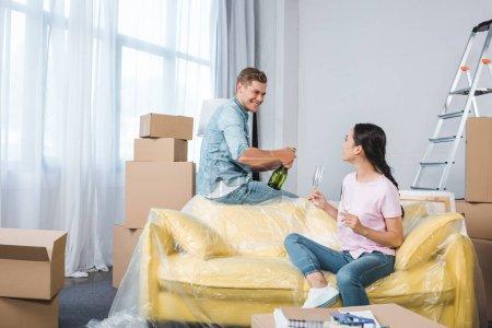 Photo pour Jeune couple souriant avec champagne célébrant après avoir emménagé dans une nouvelle maison - image libre de droit