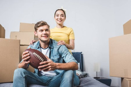 interracial young couple sitting on bed with american football ball after moving into new home