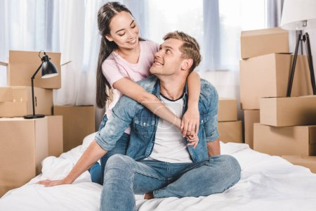 happy young couple sitting on bed after moving into new home
