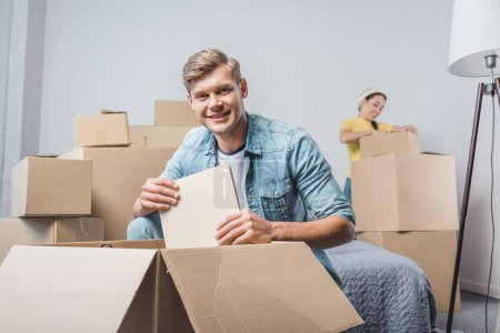 Photo for Beautiful young couple unpacking boxes while moving into new home - Royalty Free Image