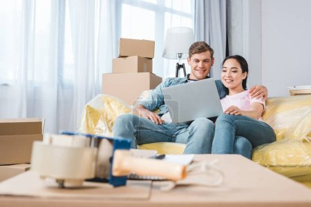 Photo for Beautiful young couple using laptop on couch while moving into new home - Royalty Free Image