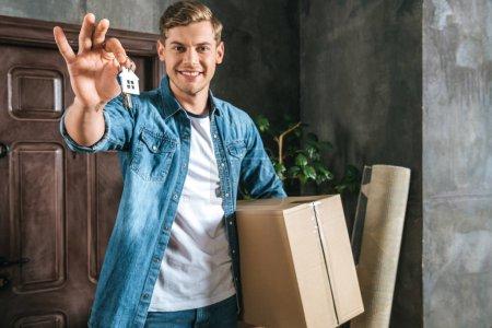 Photo pour Bel homme souriant avec boîte et clé déménageant dans une nouvelle maison - image libre de droit