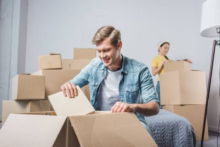 Photo for Young couple unpacking boxes while moving into new home - Royalty Free Image