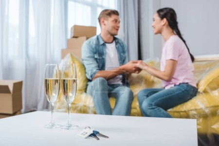 Photo for Beautiful young couple sitting on couch while moving into new home with champagne glasses and keys on foreground - Royalty Free Image