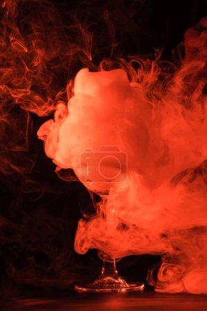 orange creativity smoke in glass on black background