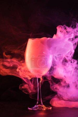 glass full of pink smoke on black background
