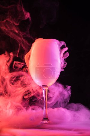 wine glass full of pink smoke on dark background