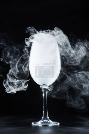wine glass with white smoke on black background