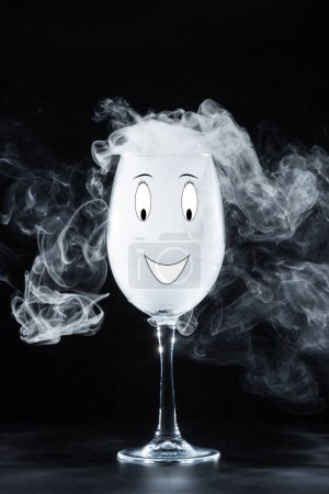 glass with white smoke and smile symbol on black background