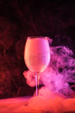 Photo pour Verre à vin avec fumée rose mystique sur fond noir - image libre de droit