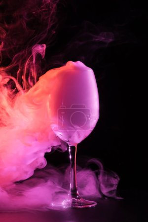 swirl of pink smoke in glass on black background
