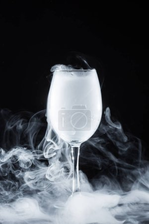 white smoke in glass on black background