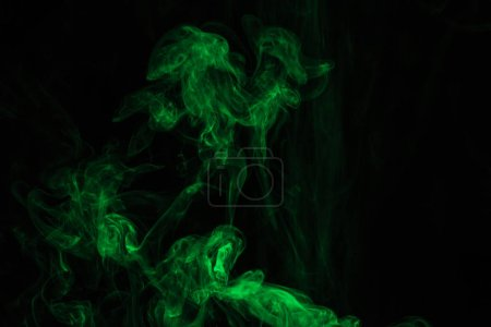 abstract mystical texture with green smoke on black