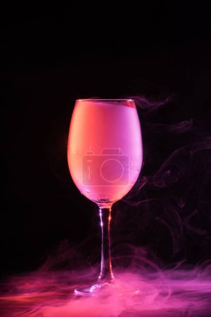 wineglass with pink smoke on black background