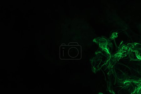 green smoke on black background with copy space