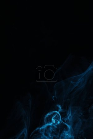 blue swirl of smoke on black background with copy space