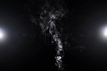 Photo pour Abstrait avec tourbillon de fumée blanche et les lumières sur fond noir - image libre de droit