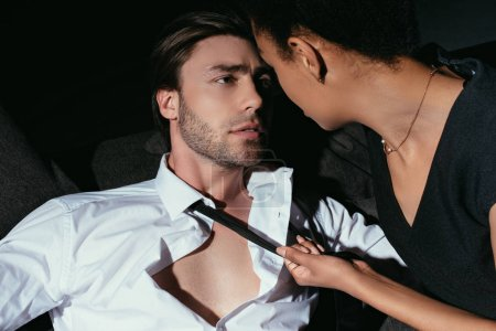 young multiracial sexy couple in black clothing looking at each other