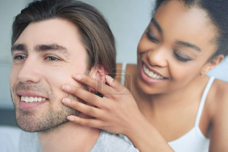 selective focus of happy multiethnic couple in love at home